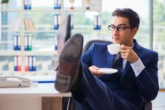 The businessman drinking coffee in the office during break. Businessman drinking coffee in the office during break Stock Photo