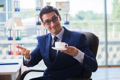 The businessman drinking coffee in the office during break. Businessman drinking coffee in the office during break Royalty Free Stock Images