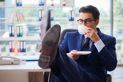 The businessman drinking coffee in the office during break. Businessman drinking coffee in the office during break Stock Photos