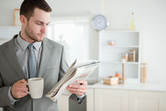 Businessman drinking coffee while reading the news Royalty Free Stock Photography