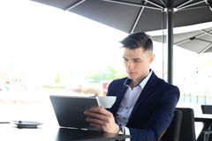 Businessman drinking coffee and reading news in cafe. Stock Photos