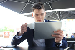 Businessman drinking coffee and reading news in cafe. Stock Photography