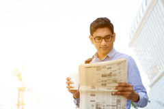 Businessman drinking coffee reading newspaper Royalty Free Stock Images