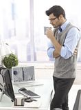 Businessman drinking coffee standing in office Royalty Free Stock Photos
