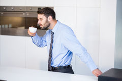 Businessman drinking coffee while standing by table Stock Photos