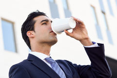 Businessman drinking coffee to go with a take away cup Royalty Free Stock Photo
