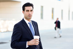 Businessman drinking coffee to go with a take away cup. Businessman with formal clothes drinking coffee to go with a take away cup. Man wearing blue suit and tie Royalty Free Stock Photography