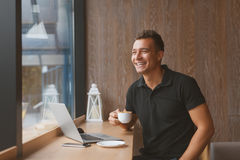 Businessman drinking coffee and using laptop in cafe Stock Photos