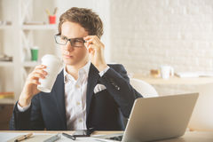 Businessman drinking coffee and using laptop. Handsome european businessman drinking coffee and using laptop in modern office. Morning concept Stock Photography