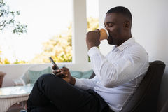 Businessman drinking coffee while using mobile phone in cafe Stock Photos