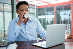 Businessman drinking coffee while working on laptop Stock Photography