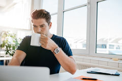 Businessman drinking coffee and working on laptop at office Stock Image