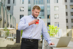Businessman drinking coffee and working on laptop outdoor.  Stock Image