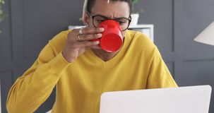 Businessman drinking coffee while working on office laptop stock video