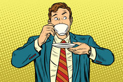Businessman drinking Cup of coffee looking sideways. Pop art retro vector illustration Royalty Free Stock Photo