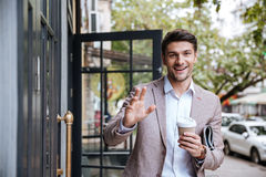 Businessman drinking cup of coffee and waving to someone Stock Photos