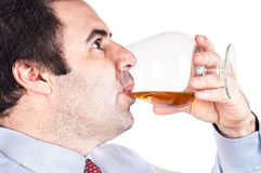 Businessman drinking a glass of whisky. A businessman drinking a glass of whisky Royalty Free Stock Photos