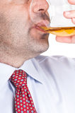 Businessman drinking a glass of whisky Stock Images