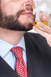 Businessman drinking a glass of whisky Stock Photography