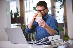 Businessman drinking office while using cellphone at creative office Royalty Free Stock Photos