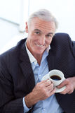 Businessman drinking and sitting in a waiting room Stock Photography
