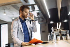 Businessman drinking water and reading paper Stock Images
