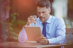 Businessman drinking water while using digital tablet Royalty Free Stock Photos