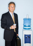 Businessman drinking water from water cooler Stock Image