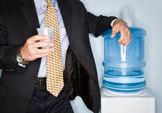 Businessman drinking water from water cooler Royalty Free Stock Photography