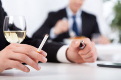 Businessman drinking wine and smoking cigarettes Royalty Free Stock Photos