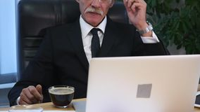 Businessman drinks coffe while watching the laptop screen.  stock footage