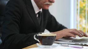 Businessman drinks coffe while watching the laptop screen.  stock video