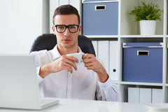 Businessman drinks coffee in office Stock Photos