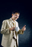 Businessman drinks tea. Joyful businessman drinks tea and shows thumb up stock photo