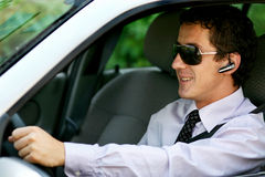 Businessman driving with bluetooth. Smiling businessman driving with his car with bluetooth handsfree royalty free stock images
