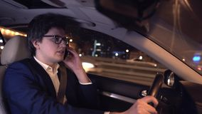 Businessman driving car at night and talking on his smartphone danger. Young businessman in glasses driving his car in a night city while talking on the phone stock footage