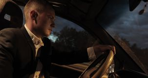 Businessman driving a car through streets of night city. stock footage
