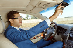 Businessman driving his car. Businessman adjusting the rearview mirror while driving a car Royalty Free Stock Image