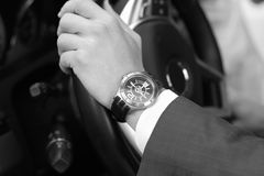 Businessman driving his car, hand on the steering wheel. Hand wi. Th golden watch. Business concept Stock Image