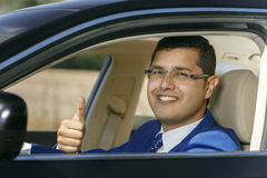 Businessman driving his car. Handsome businessman showing thumbs up while sitting in the car Stock Image