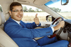 Businessman driving his car. Businessman showing a thumbs up while sitting in the driver's seat Royalty Free Stock Image