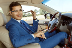 Businessman driving his car. Businessman wearing seat belt in his new car Stock Image