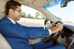 Businessman driving his car. Young handsome businessman driving his new car Stock Photo