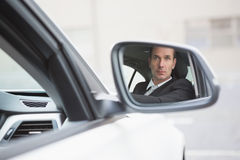 Businessman driving with his reflection in rear view mirror Royalty Free Stock Photography