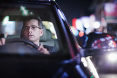 Businessman driving at night in the city Stock Photography