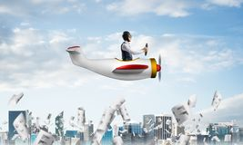 Businessman driving propeller plane above downtown royalty free stock images