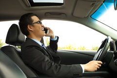 Businessman driving and talking on the phone Stock Photos