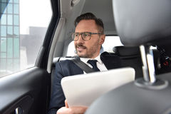 Businessman driving in taxi using tablet Stock Images