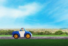 Businessman driving a toy car Stock Images