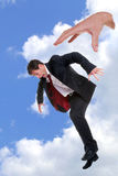 Businessman dropped by the hand of God. Concept photo of a businessman being dropped out of the sky by the hand of God, could be used to portray themes such as Stock Image